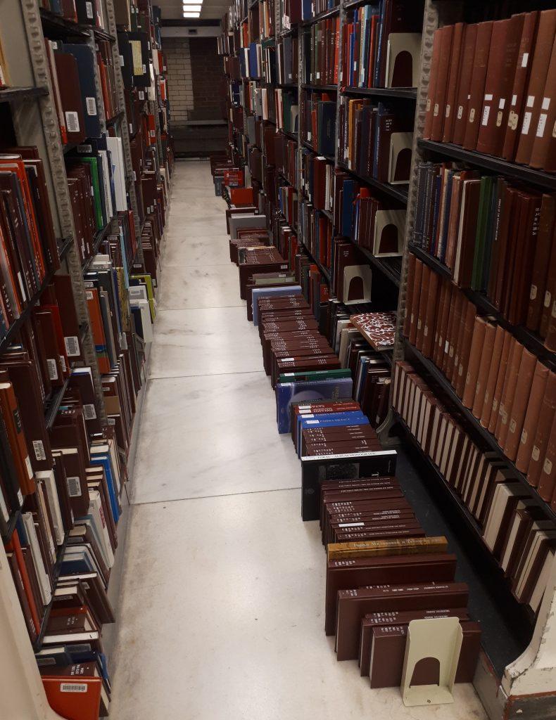 Täysiä kirjahyllyjä ja lattialla oleva kirjarivistö Library of Congressissa.