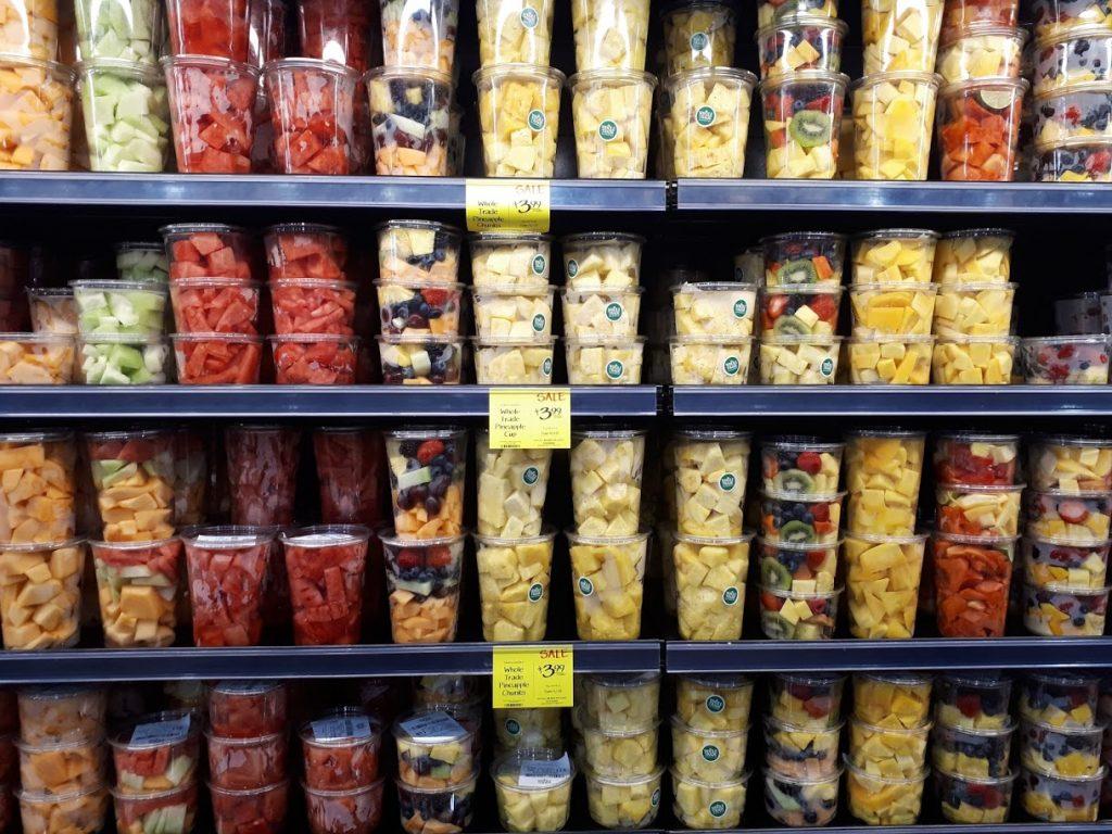 Hedelmiä muovirasioissa ruokakaupan hyllyllä.